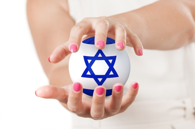 Две руки женщины, защищая сферы земного шара флага израиля на белом фоне.