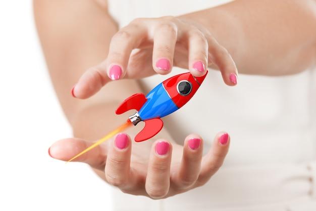 흰색 바탕에 현대 만화 로켓을 보호 하는 두 여자 손. 3d 렌더링