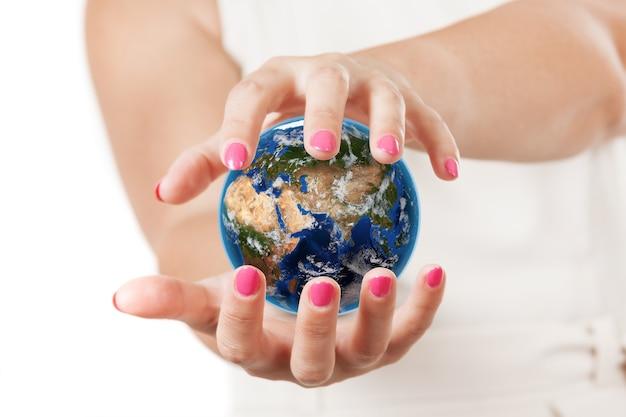 白い背景の上のプラネットアース世界の地球を保護する2つの女性の手。 nasaから提供されたこの画像の要素。 3dレンダリング