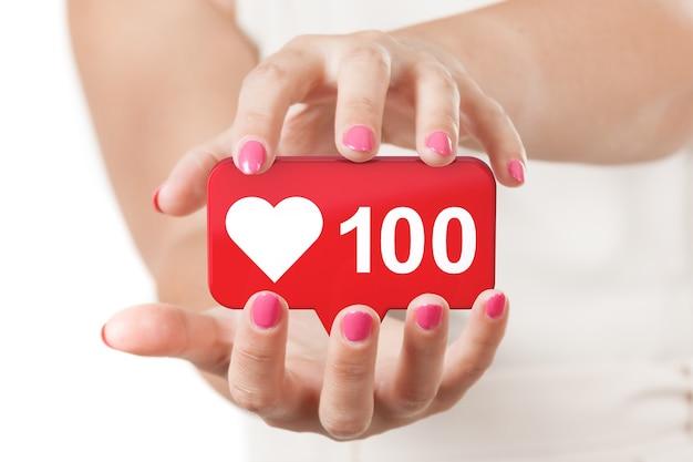 흰색 바탕에 빨간색 소셜 미디어 네트워크 사랑과 같은 심장 아이콘을 보호하는 두 여자 손. 3d 렌더링