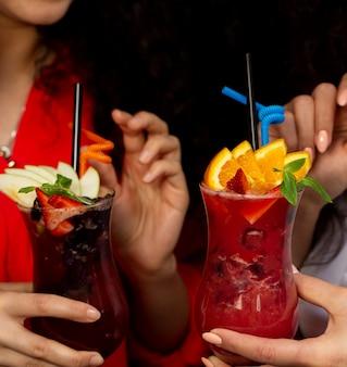 Две женщины держат бокалы с фруктовыми коктейлями с апельсином, клубникой и яблоком, клубникой