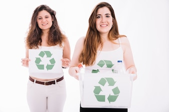 Two woman holding recycle placard and crate against white background