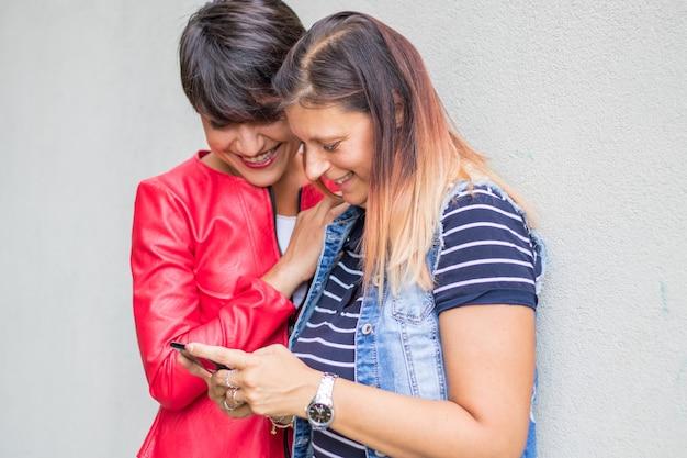 カジュアルなドレスを着た2人の女性がメッセージを読んでtgecallphoneを探しています