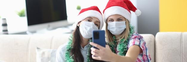 Две женщины в защитной маске делают селфи по телефону.