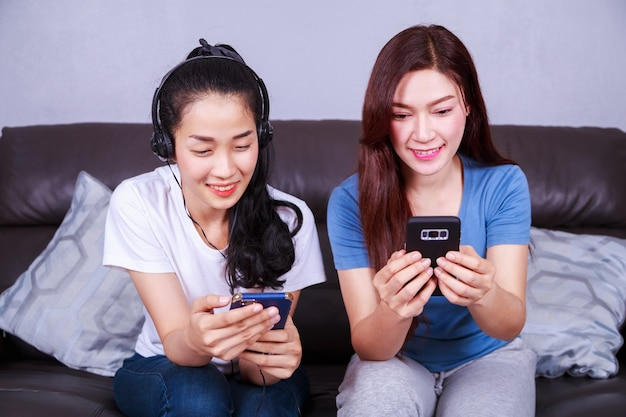 Two woman listening to music in headphones with mobile on sofa at home