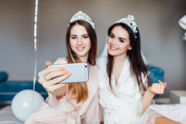 二人の女性が寝室で自分撮りをし、良いヘンパーティーをします