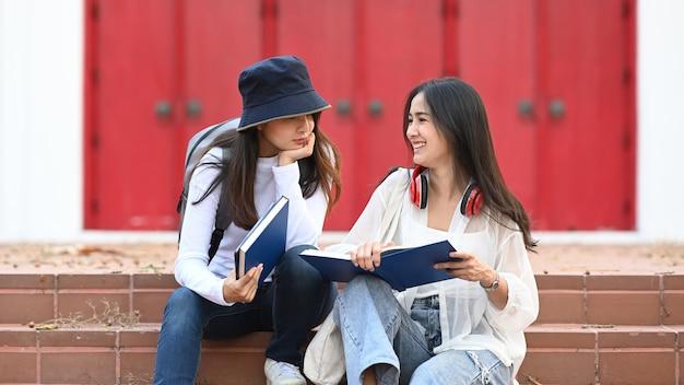 Две женщины читают книгу и сидят в парке