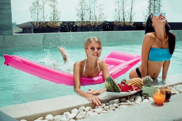 Two woman relaxing on luxury tropical vacation near with big plates with different tasty sweet exotic fruits in the pool, travel and eating healthy, vegan vegetarian lifestyle, diet concept.