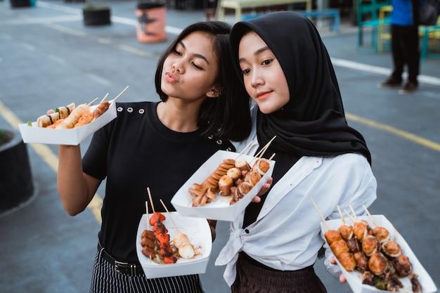 두 여자는 한국 길거리 음식 접시를 제공