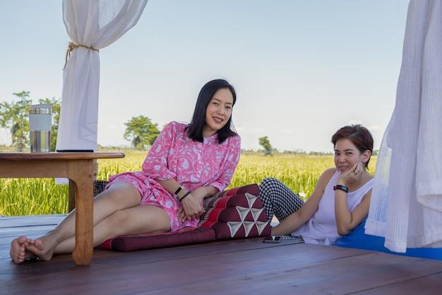 두 여자는 여름에 자연 경관을 감상할 수 있는 파빌리온의 나무 바닥에 앉아 있다