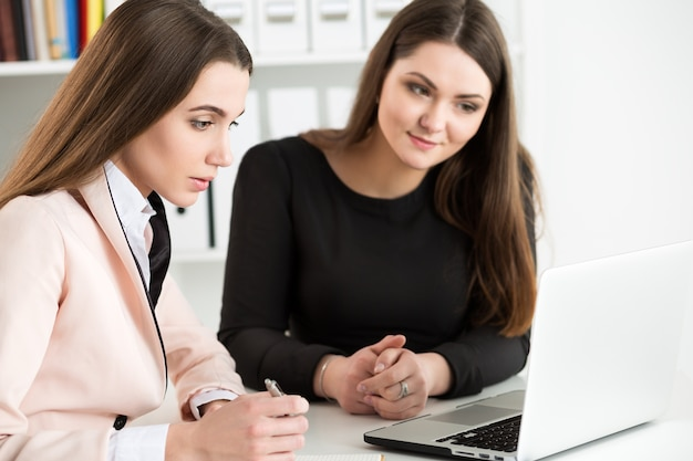 Two woman sitting at office and looking at laptop monitor discussing some questions