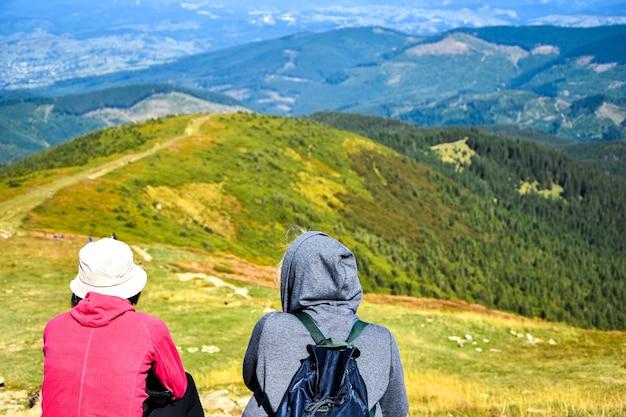 Две женщины, сидящие на горе. вид сзади двух туристов с рюкзаками. безликий. цели походов и досуга. концепция путешествия