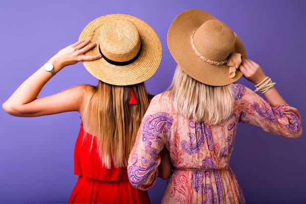 Due donne stanno tornando alla telecamera, eleganti abiti estivi boho abbinati a colori, abbracci e cappelli di paglia, concetto di accessori di moda.