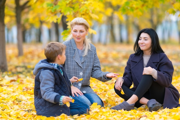 Two woman and teenage boy in park sitting on the ground covered with bright yellow leaves and chatting together