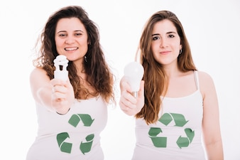 Two woman wearing recycle icon tanktop showing fluorescent bulb and led bulb