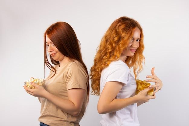 팝콘과 감자 칩과 함께 그릇을 숨기고 흰 벽에 포즈 두 여자 친구