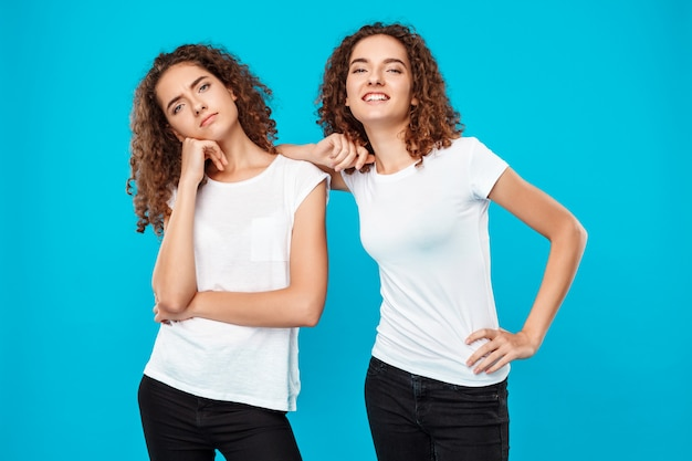 Two womans twins posing over blue. one displeased, another smiling.