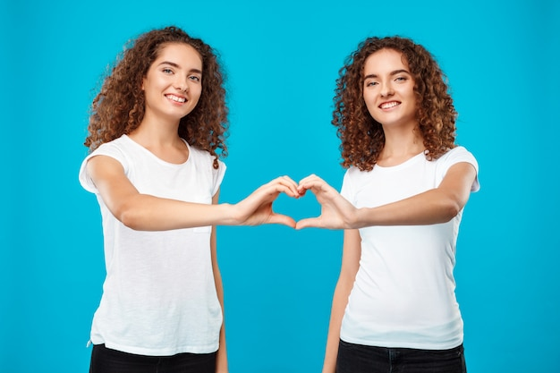 Two womans twins showing heart with hands over blue.