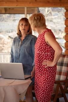 55세의 두 여성이 노트북을 들고 테이블 근처에 서서 그들의 계획에 대해 이야기합니다