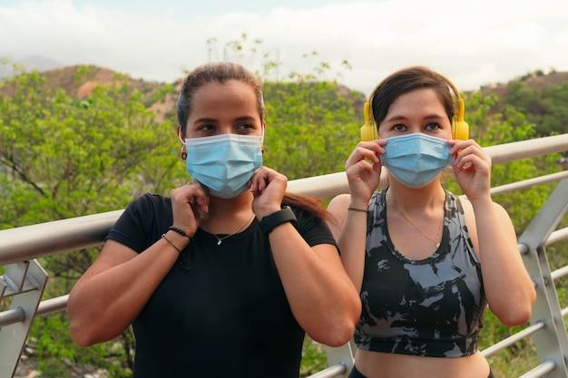 2人の女性は、屋外でトレーニングしているときに保護マスクを調整します。