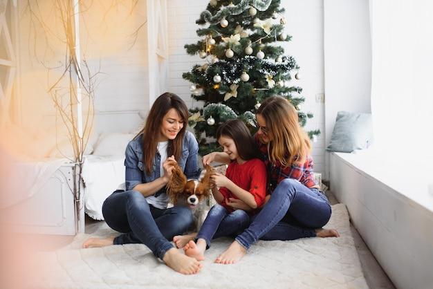 Две женщины и девочка с собакой веселятся возле елки в рождественские праздники.