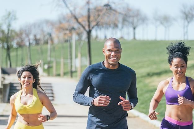 두 여자와 마스크를 쓴 남자가 공원을 달리고 있습니다. 전면보기.
