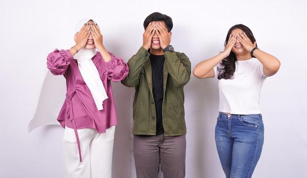 Две женщины и мужчина закрывают глаза на белом фоне