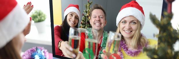 手にシャンパンのグラスとサンタクロースの帽子をかぶった2人の女性と男性は幸せな友人を祝福します
