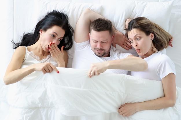 두 여자와 한 남자가 침대에 누워