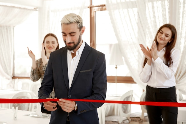 Two women are clapping hands when the handsome business man is officially cutting red ribbon
