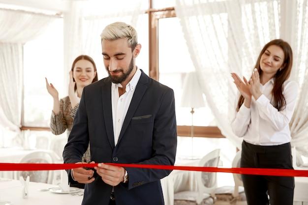 ハンサムなビジネスマンが公式に赤いリボンを切っているとき、2人の女性が手をたたく