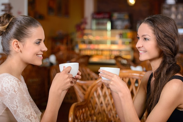 Two women are drinking tea and talking in cafe.
