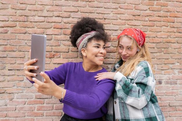 Две женщины подружки фотографируются на улице