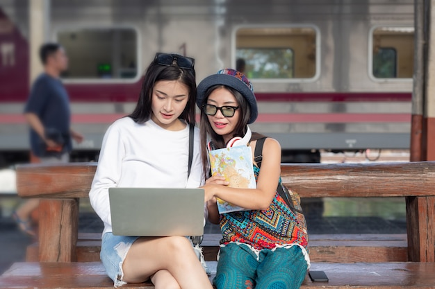 Two women are happy playing a notebook while traveling at the train station. tourism concept