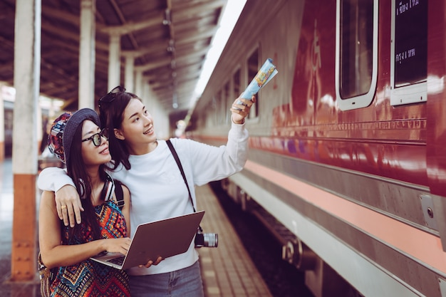 Two women are happy while traveling at the train station. tourism concept