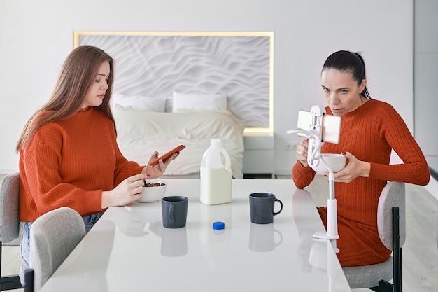 두 여성이 주방의 식탁에서 아침 식사를하고 스마트 폰에서 정보를 검색하고 있습니다.