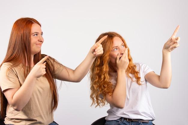 두 여자는 재미 있고 그들은 멀리 흰 벽을보고 집게 손가락을 가리킨다