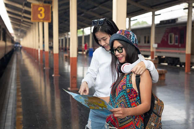 Two women are holding the map while waiting for the train. tourism concept