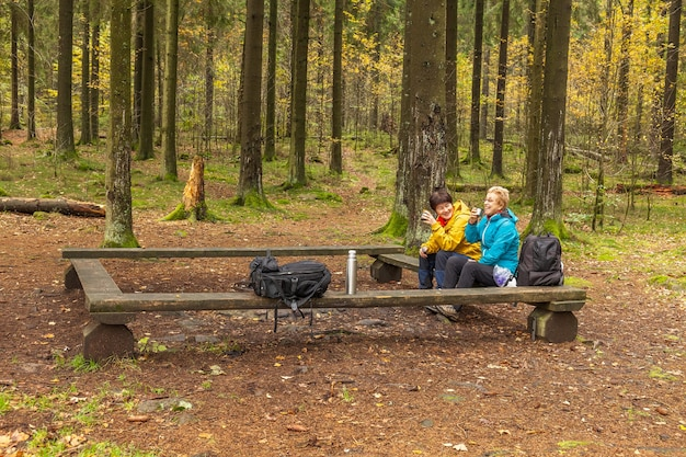 Two women are laughing, sitting on a bench in forest drink tea or coffee from a thermos