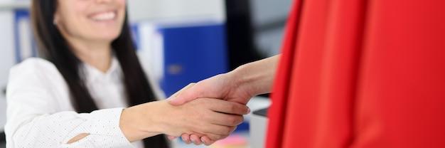 Две женщины трясутся в офисе. деловое соглашение между концепцией партнеров