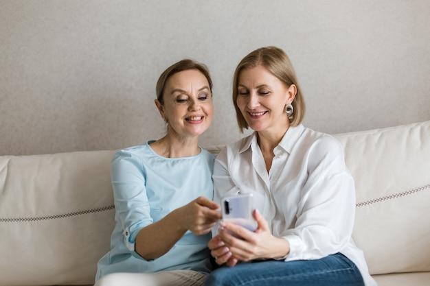 Две женщины сидят на диване и смотрят в телефон во время разговора