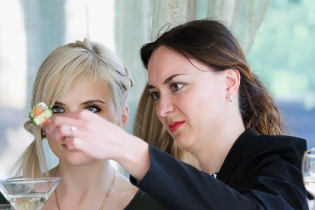 Две женщины на фуршете щепетильно относятся к еде