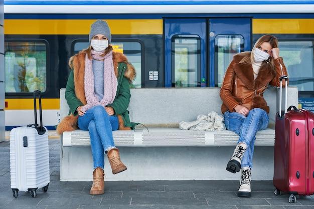 Covid-19 제한으로 인해 마스크를 쓰고 기차역에서 두 명의 여성
