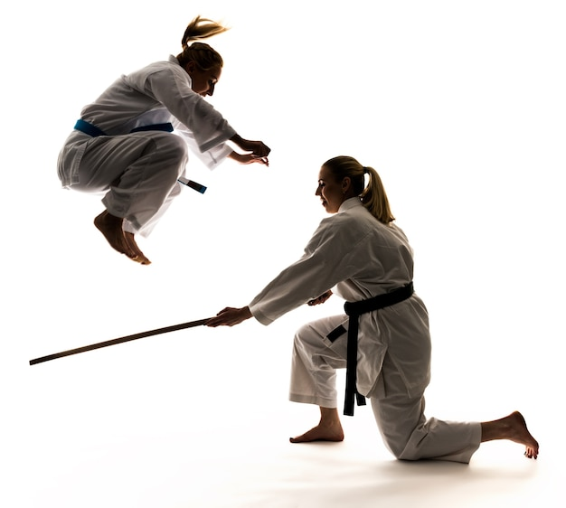 스포츠 도구를 사용하여 가라테 훈련에 두 여자 선수. 흰색 바탕에 여자 점프의 사진