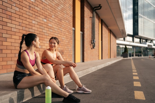 Две женщины перед городской тренировкой. девушки готовятся к бегу и сидят на улице.