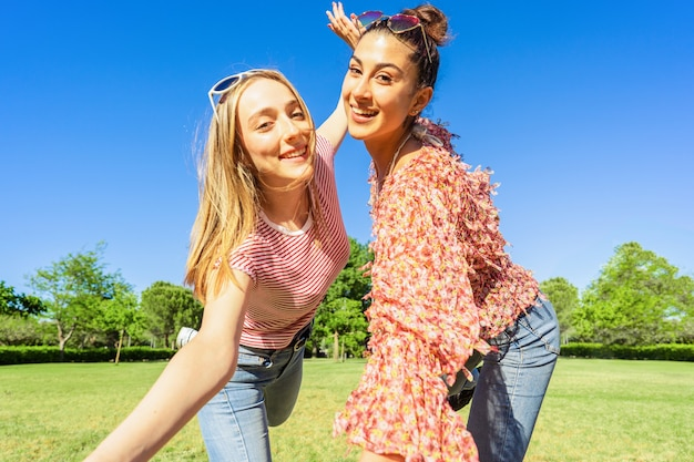 Two women best friends having fun in a city park posing for a happy selfie smiling looking at camera. two homosexual student girl enjoying diversity joking together outdoor in the green of nature