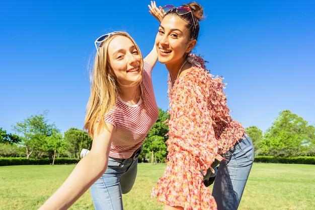 カメラを見て笑顔で幸せな自分撮りのポーズをとって都市公園で楽しんでいる2人の女性の親友。自然の緑の中で屋外で一緒に冗談を言っている多様性を楽しんでいる2人の同性愛学生の女の子