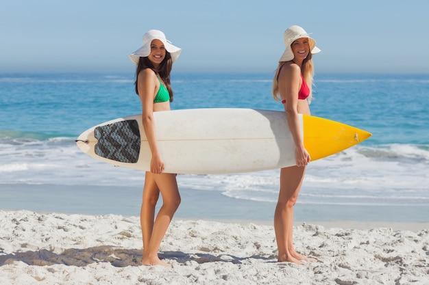 Two women in bikinis holding a surfboard
