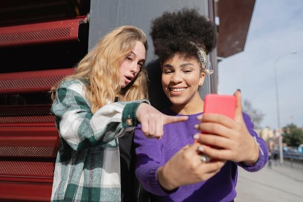 金髪の女性とアフロの女性の2人の女性がスマートフォンで自分撮りをしています