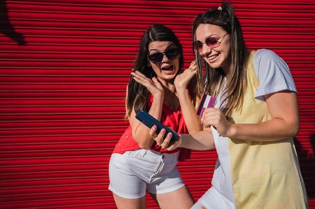2人の女性が携帯電話とクレジットカードに驚いて購入します。